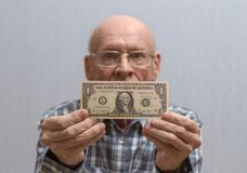 An old bald man with glasses holds a banknote in front of him - one US dollar. Concept Front view royalty free stock photo
