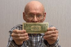 An old bald man with glasses holds a banknote in front of him - one US dollar. Concept Front view stock photography