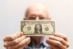 An old bald man with glasses holds a banknote in front of him - one US dollar. Concept Front view royalty free stock images