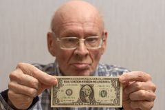 An old bald man with glasses holds a banknote in front of him - one US dollar. Concept Front view stock image