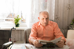 Old Bald Man Reading Newspaper at the Table Royalty Free Stock Photo