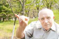 Old bald man. Showing his pinky finger over the green nature background Royalty Free Stock Photography