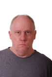 Old Balding Man Looking Stern. An older balding man in a gray shirt with a stern look Stock Photography
