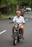 Old Balinese on motorcycle. BALI - JANUARY 24. Old traditional Balinese man on bike in Bali on January 24, 2012 in Bali, Indonesia. Most Balinese people cannot Stock Photography