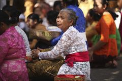 An old Balinese woman in traditional clothes on Hindu Temple ceremony, Bali Island, Indonesia stock photography