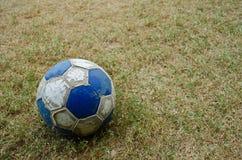 An old ball. An old football on the ground Stock Photos