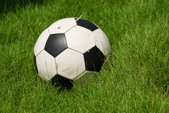 Old ball. Old football ball on a green grass stock images