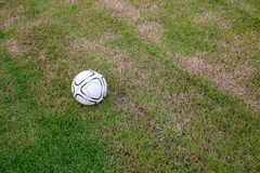 Old ball on the artificial turf at the stadium. view of green striped football. Field with soccer ball royalty free stock images