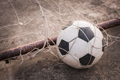 Old ball in the goal net Royalty Free Stock Images