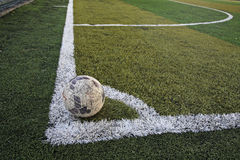 Old ball in new soccer field at corner Royalty Free Stock Image