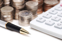 Old ball pen on calculator and stack coins background Stock Photos