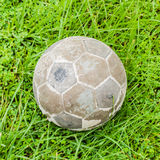 Old ball put on green grass. Take on top Stock Images