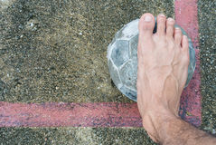 Old ball put no conner in football field. And one foot on top Royalty Free Stock Image