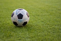 Old ball soccer on new green grass-ground Stock Images