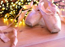 Old Ballet Shoes. Nostalgia concept. A pair of pink, old ballet shoes. Nostalgia background. Old ballet shoes on wooden table with blurred, yellow, warm lights royalty free stock photography