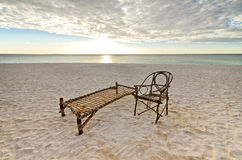 Old Bamboo Chair  and Camp Bed on Sandy Beach Stock Image