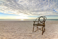Old Bamboo Chair on Sandy Beach with Sunset Royalty Free Stock Images