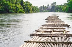 Old bamboo raft is floating on the river in the thailand Royalty Free Stock Image