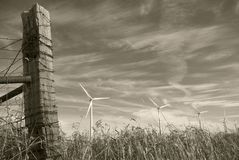 Old Barbed Wire Fence Post and Wind Turbines Stock Photography