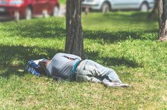 Old barefoot homeless or refugee man sleeping on the grass in the city park using his travel bag as pillow, social documentary str. Eet concept Royalty Free Stock Photography