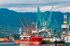 Old Barge Freight Ship Tanker And Heavy Loading Cranes Jib In Port Royalty Free Stock Image