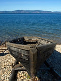 The old barge. Wooden boat on the shore isolated on the blue background of the water and the sky Stock Images