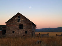 Old Barn. This is an image of an old barn, long abandoned, with fencing and the moon during an early morning in NW Montana Royalty Free Stock Photos