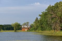 Old barn along shoreline of a lake Stock Photo