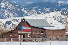 Old Barn with American Flag. An Old Weathered Barn with an American Flag set in the Mountains Stock Image