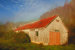 Old barn in autumnal forest. Scenic view of old barn in autumnal forest with blue sky and cloudscape background, Glen Affric, Inverness, Scotland Stock Images