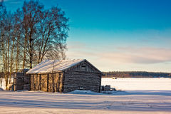 Old Barn Bathing In The Winter Sun. An old barn house and wooden crates unders the bright winter sun on the fields of the Northern Finland Royalty Free Stock Image