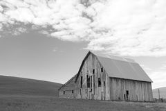 Old Barn in Black and White. Old dilapidated barn in hilly field with sky filled with puffy clouds in background in Palouse area of Washington State in black and Royalty Free Stock Photo