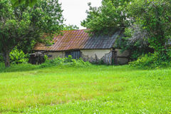 Old barn and bright green vegetation beside him. Old barn with brown roof and bright green vegetation around it Royalty Free Stock Images