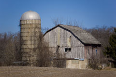 Old barn building. Old faded red barn with silo empty field and blue sky Royalty Free Stock Photography