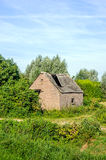 Old barn with collapsed roof of corrugated asbestos cement sheet Stock Photography