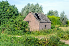 Old barn with collapsed roof of corrugated sheets made with asbe Royalty Free Stock Image