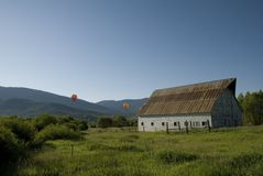 Old barn in Colorado. An old barn in a field in Steamboat Springs Colorado with a hot air balloon in the distance royalty free stock photos