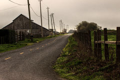 Old barn on a country road. Dramatic picture of an old barn under powerlines Stock Photography