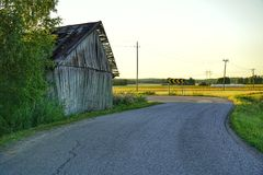 Old barn in countryside. Not in use. Poor condition. Historical. Countryside road going through fields royalty free stock photography