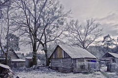 Old barn covered by snow under the oak trees Stock Photography