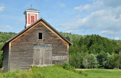 Old Barn With Cupola. Old weathered wooden barn with a red cupola in a field in Vermont Royalty Free Stock Photography