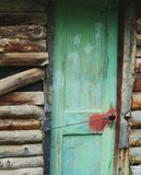 Old Barn Door. Old, green, paint stained barn door on an old wooden building falling apart Royalty Free Stock Photos