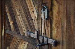 Old Barn Door with Metal Lock. An old barn door stands locked with an antique metal lock Royalty Free Stock Photos