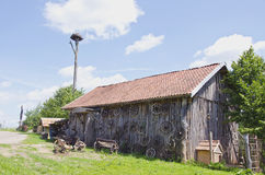 Old barn in farm with carriage wheel Royalty Free Stock Photography