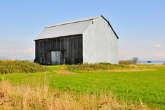 An old barn in a farm field Stock Photos