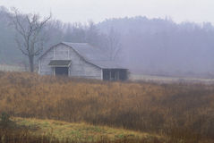 Old Barn in Field. An old barn in a field on a misty day Stock Photo