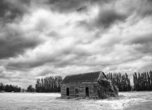 Old Barn in Field Infrared. An infrared photo of a dilapidated barn covered in creepers in a field outside Greytown, New Zealand. A grey stormy sky lies above Royalty Free Stock Photography