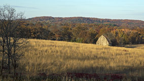 Old barn. In a field in the late afternoon Royalty Free Stock Photo