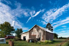 Old barn in front of a blue sky royalty free stock photo