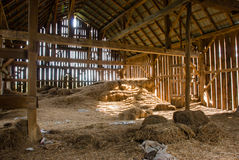 Old barn full of hay. Old wooden barn full of old hay with light shining through the wooden boards Stock Photography